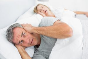 Man covering his ears next to snoring wife