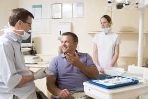 Dentist and assistant in exam room with man in chair smiling