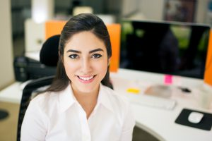Smiling young woman at desk