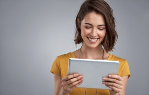Smiing woman looking at tablet