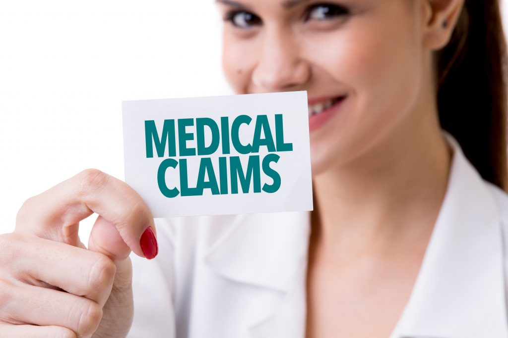 Woman holding up a card reading medical claims