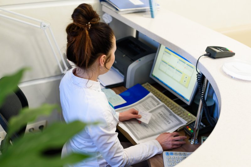 A woman sitting at a computer behind a desk