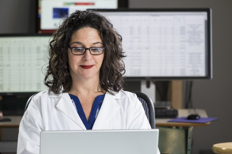 A middle-aged woman wearing a white medical coat sitting behind a computer