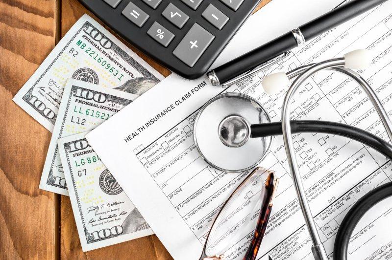 A calculator, stethoscope, money, a pen, and a health insurance claim form lying on a desk