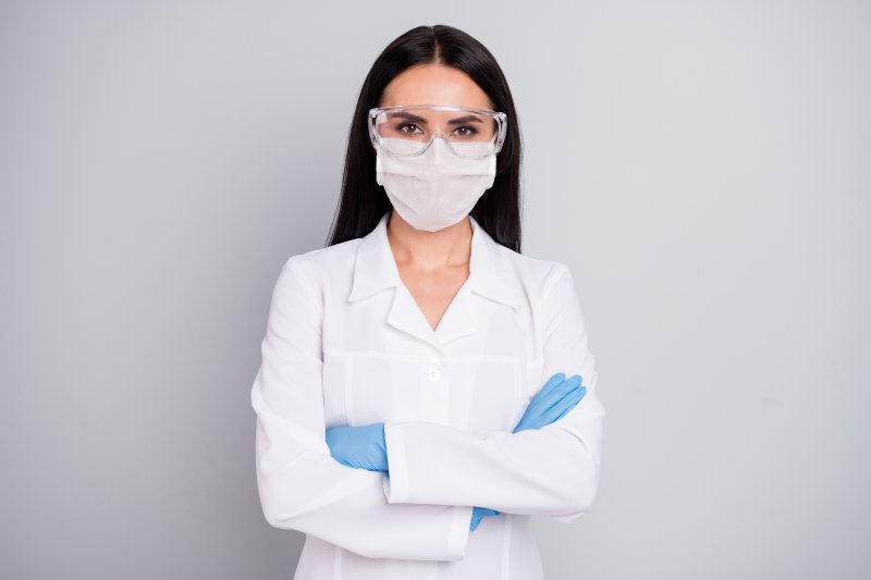 A female dentist wearing personal protective equipment and standing with her arms crossed