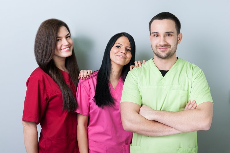 Three dental professionals standing next to each other and smiling, all wearing different colored scrubs