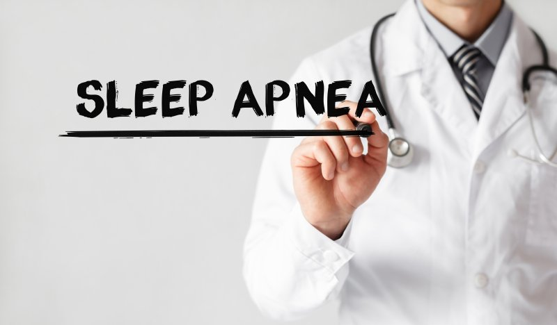 "A doctor wearing a lab coat and stethoscope writing the words ""Sleep Apnea"""