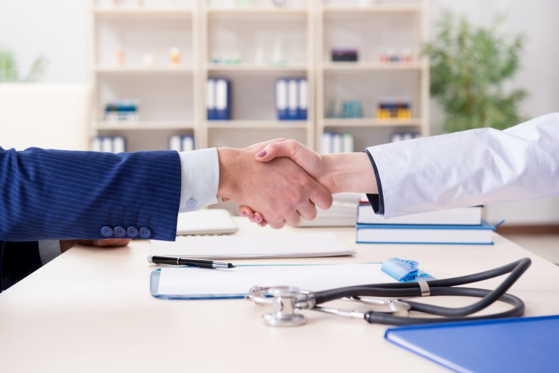 Two people shaking hands across a table that contains paperwork, a stethoscope, and books
