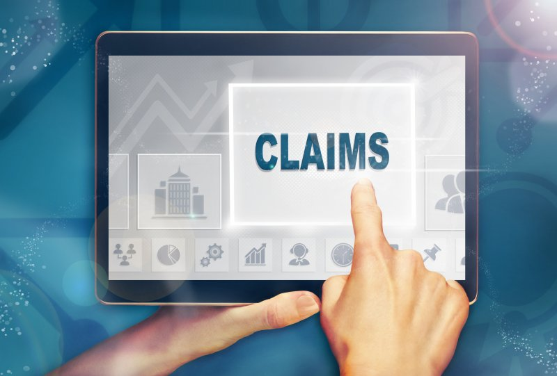 "A digital image of a person using a tablet and the word ""Claims"" appearing on the screen"