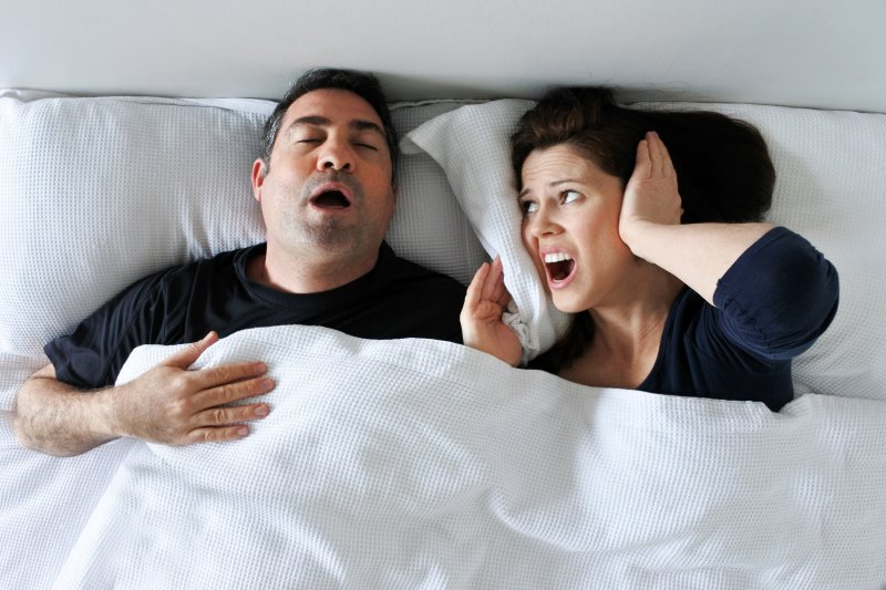 a man and woman lying in bed while he snores and she covers her ears
